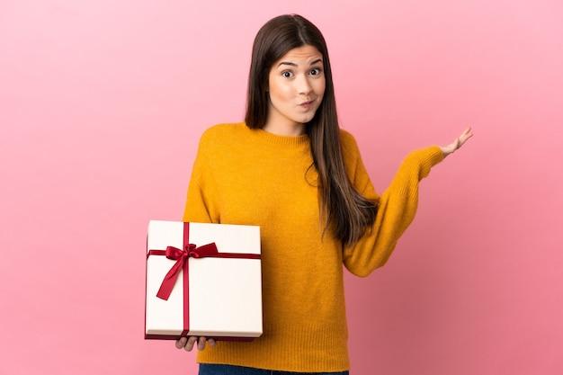 Menina brasileira adolescente segurando um presente sobre um fundo rosa isolado, tendo dúvidas enquanto levanta as mãos