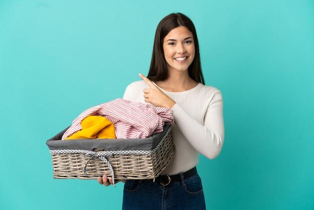Menina brasileira adolescente segurando uma cesta de roupas isolada em um fundo azul apontando para o lado para apresentar um produto