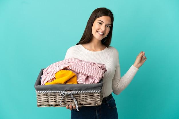 Menina brasileira adolescente segurando uma cesta de roupas isolada em um fundo azul apontando para trás