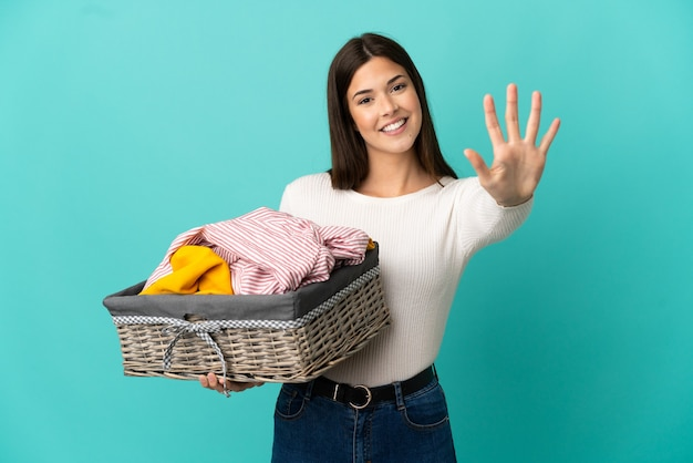 Menina brasileira adolescente segurando uma cesta de roupas isolada em um fundo azul, contando cinco com os dedos