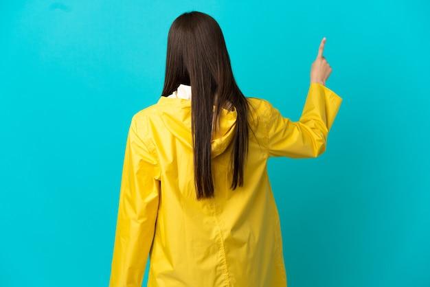 Menina brasileira adolescente vestindo um casaco à prova de chuva sobre um fundo azul isolado apontando para trás com o dedo indicador