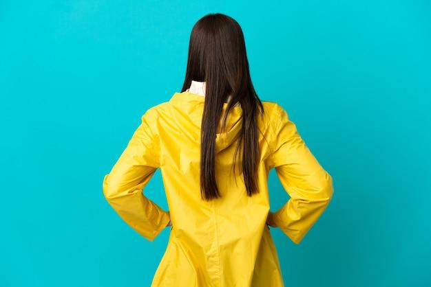 Menina brasileira adolescente vestindo um casaco à prova de chuva sobre um fundo azul isolado na posição traseira