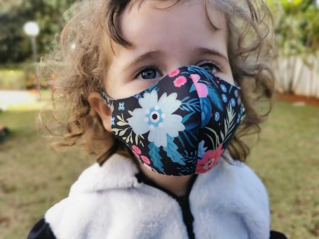 Menina brasileira sorrindo usando máscara ao ar livre.