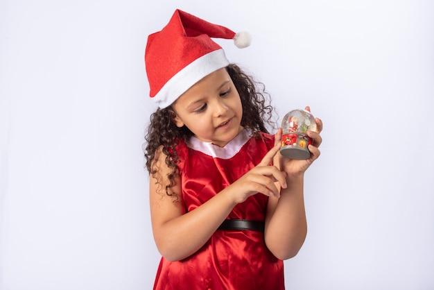 Menina brasileira vestida com fantasia de natal segurando globo de neve