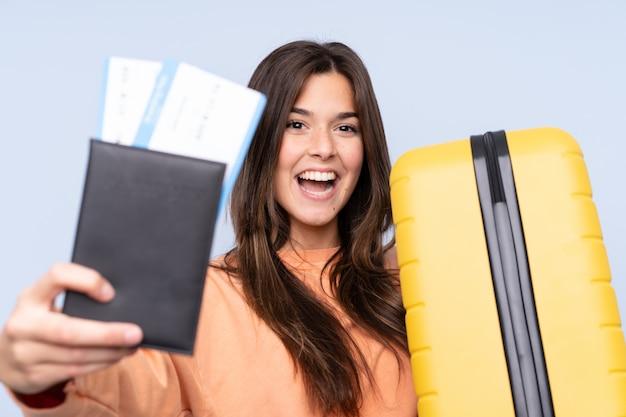 Menina brasileira viajante segurando uma mala e um passaporte