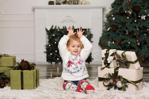 Menina brinca com decorações de pinhas para a árvore de natal.