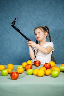 Menina brinca com frutas e tira uma selfie ao telefone. vitaminas e alimentação saudável para crianças.