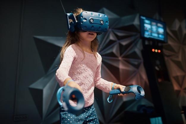 Menina brinca com óculos de realidade virtual, detém o controlador nas mãos, na sala de jogos