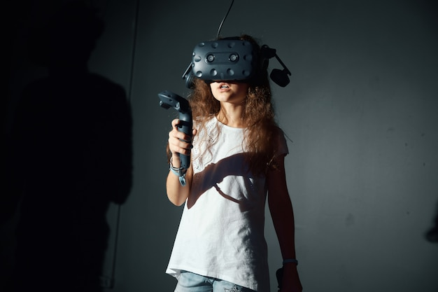 Menina brinca com óculos de realidade virtual, detém o controlador nas mãos