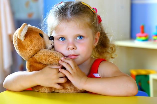 Menina brinca com um ursinho de pelúcia