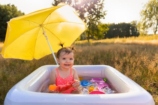 Menina brinca na piscina inflável.