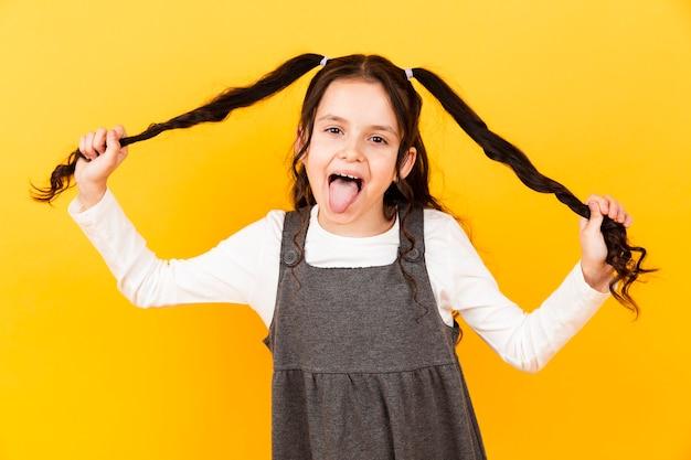 Menina brincalhão com a língua de fora enquanto segura o cabelo de tranças