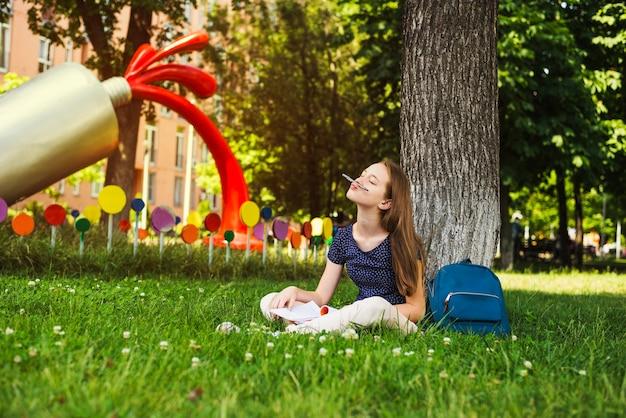Menina brincalhão com estudos sobre gramado