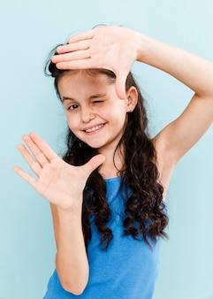 Menina brincalhão, mostrando a forma da câmera com as mãos