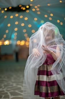 Menina brincalhão no véu branco