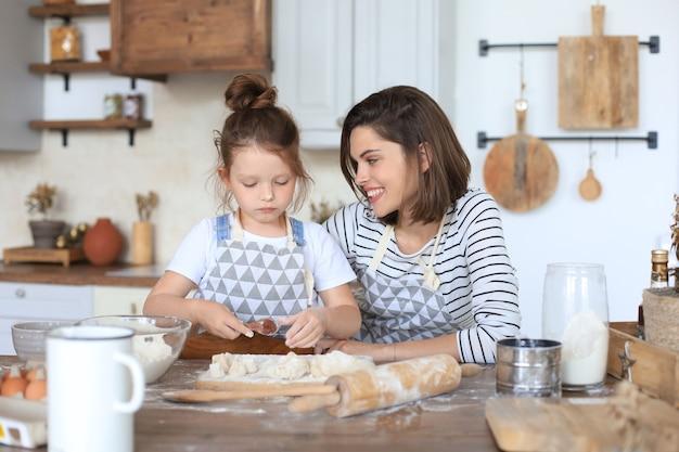 Menina brincalhona cozinhando na cozinha com sua mãe amorosa.