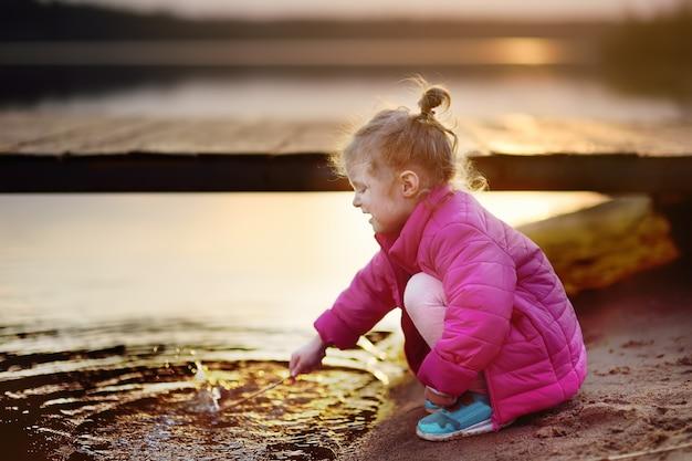 Menina brincando com água e ficar durante a caminhada pelo lago