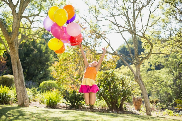 Menina brincando com balões no parque