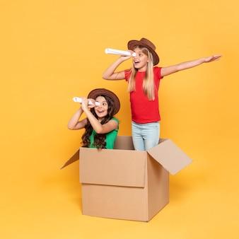 Menina brincando com binóculos de papel
