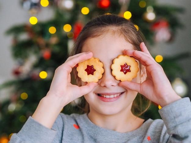 Menina brincando com biscoitos debaixo da árvore de natal na sala com luzes de natal