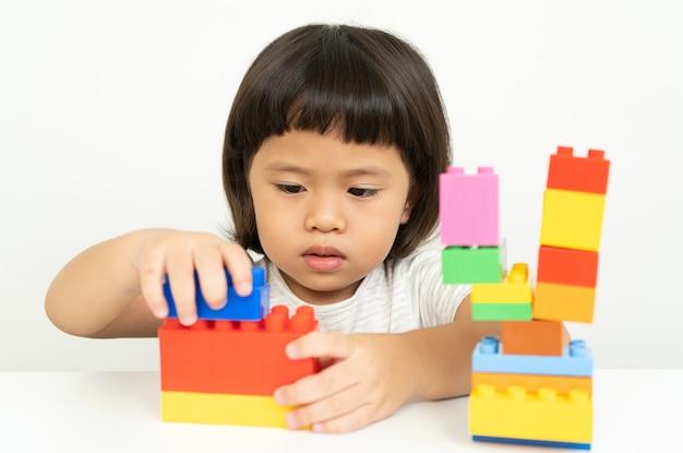 Menina brincando com blocos de brinquedo coloridos em branco, crianças brincam com brinquedos educativos