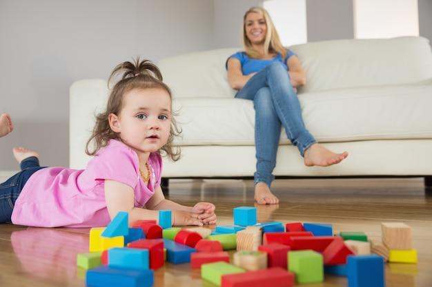 Menina brincando com blocos de construção enquanto mãe na concha