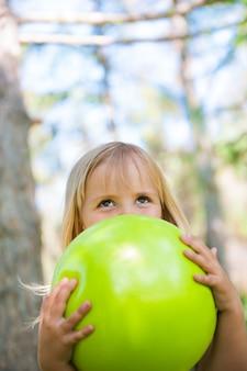 Menina brincando com bola verde no parque