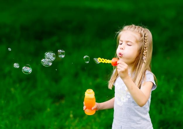 Menina brincando com bolhas de sabão.
