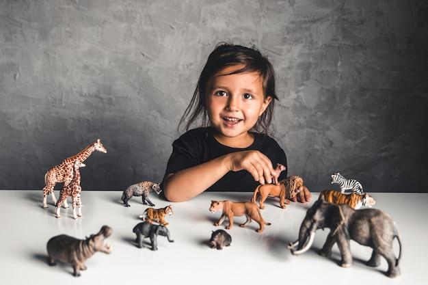 Menina brincando com brinquedos de animais na sala de jogos