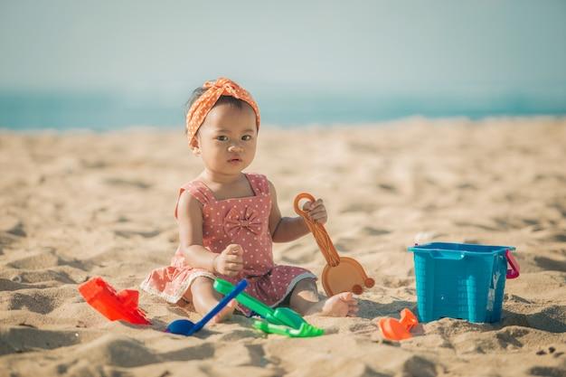 Menina brincando com brinquedos de praia na praia