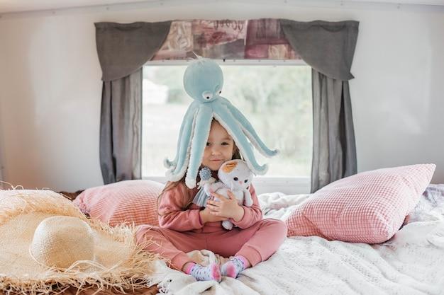 Menina brincando com brinquedos na cama no trailer de viagem
