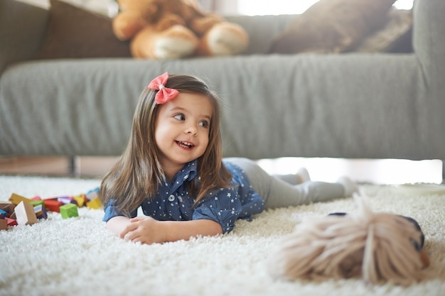 Menina brincando com brinquedos na sala