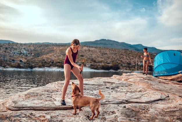 Menina brincando com cachorro na praia rochosa
