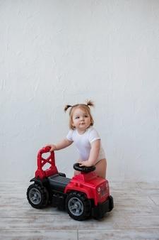 Menina brincando com carro vermelho