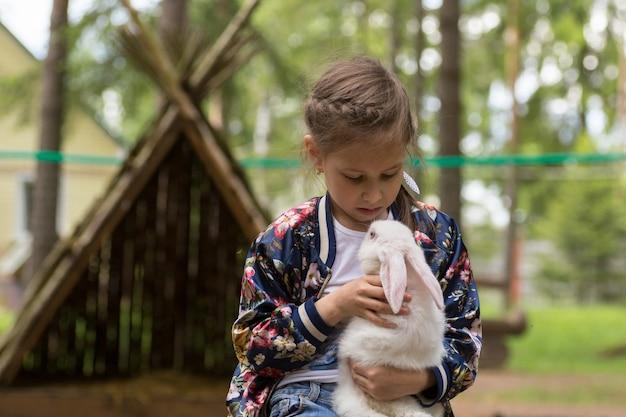 Menina brincando com coelho branco ao ar livre