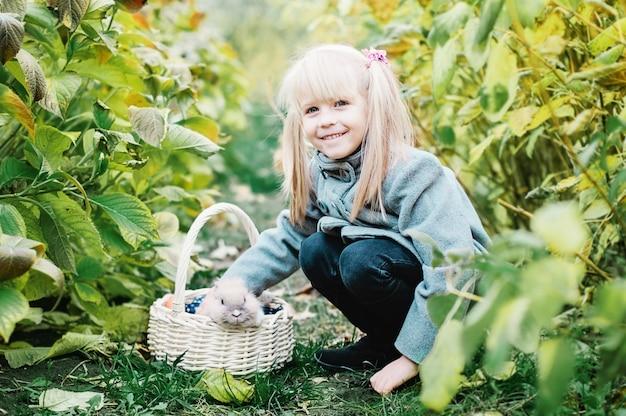 Menina brincando com coelho cinza ao ar livre
