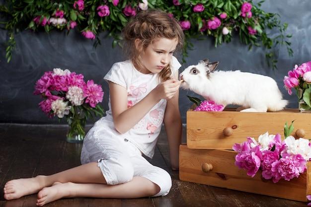 Menina brincando com coelho de verdade. criança e coelhinho branco na páscoa. criança criança alimentando animal de estimação. crianças e animais de estimação brincam. diversão e amizade para animais e crianças.