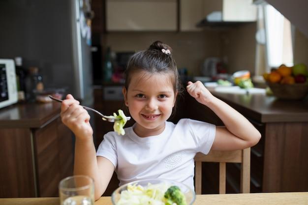 Menina brincando com comida enquanto come