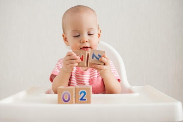 Menina brincando com cubos de madeira com números brilhantes 2022