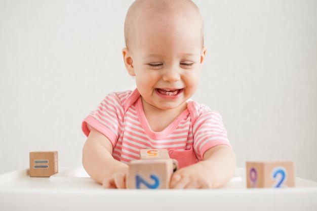 Menina brincando com cubos de madeira com números brilhantes