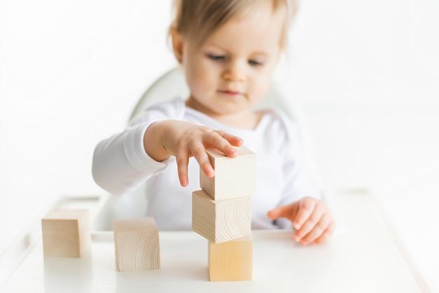 Menina brincando com cubos de madeira pela mão esquerda. jogando a criança isolada no fundo branco. jogos para crianças, educação pré-escolar. feche acima, foco seletivo