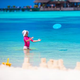 Menina brincando com disco voador na praia branca