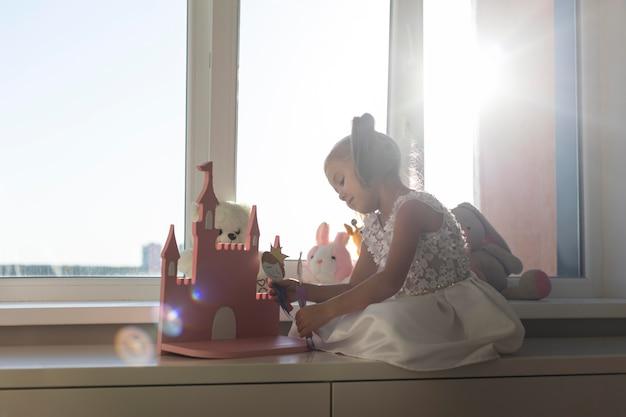 Menina brincando com fantoches em casa