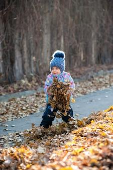 Menina brincando com folhas no parque