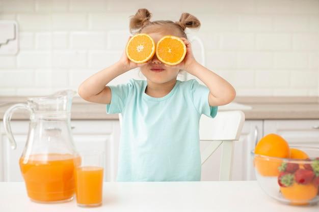 Menina brincando com laranja