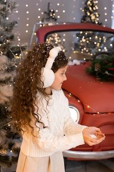 Menina brincando com neve perto de um carro vermelho e árvores de natal com luzes. feliz natal e boas festas