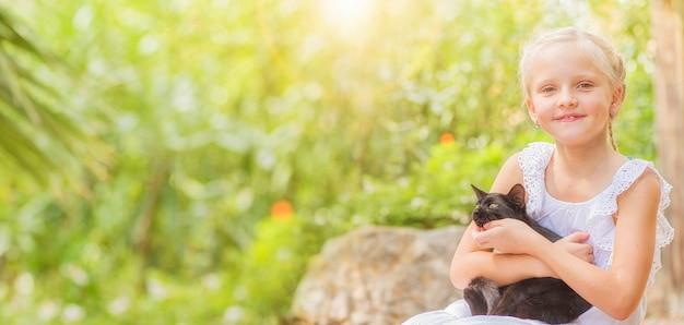 Menina brincando com o animal de estimação ao ar livre no jardim. natureza de verão