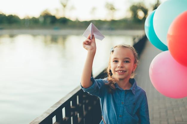 Menina brincando com o avião de papel de brinquedo