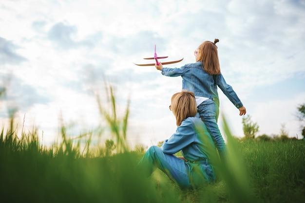 Menina brincando com o avião perto da mãe