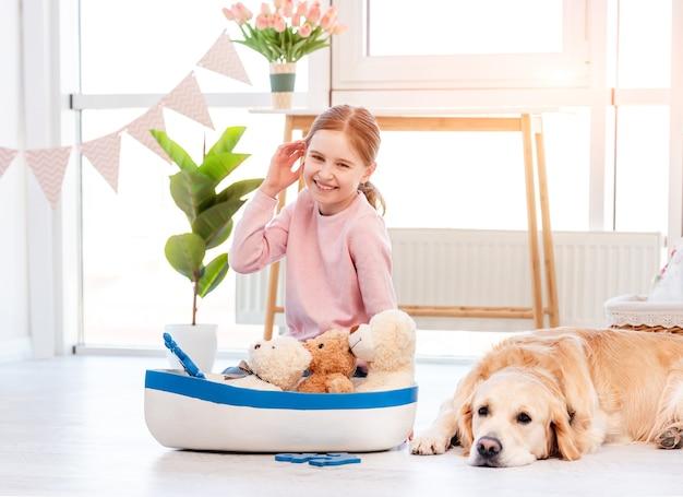 Menina brincando com o brinquedo do navio do mar e o cachorro golden retriever deitado perto dela